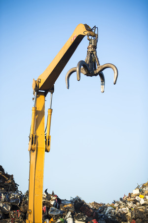 grabber: Crane claw on top of pile with scrap metal in recycling center