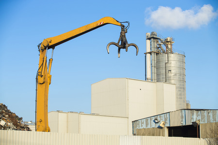 Crane picking up scrap metal in recycling site outdoors photo