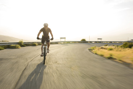 mountain road: Cyclist man riding mountain bike in sunny day on a mountain road. Image with flare. Stock Photo