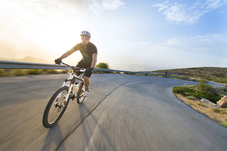 Cyclist man riding mountain bike in sunny day on a mountain road. Image with flare. Stockfoto