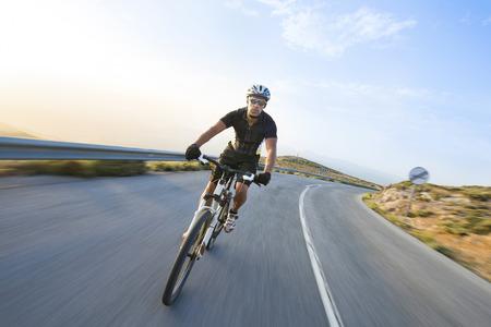andando en bicicleta: Hombre Ciclista que monta en bicicleta de monta�a en un d�a soleado en una carretera de monta�a