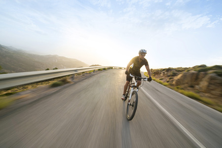Cyclist man riding mountain bike in sunny day on a mountain road. Image with flare. Standard-Bild