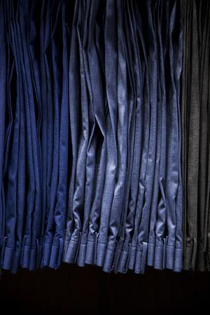 Male pants hanging on a clothes hanger inside a clothing store. Suit pants. Banco de Imagens