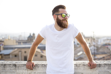 Bearded man posing in the street with sunglasses. Stock Photo