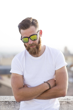 Bearded man posing in the street with sunglasses. Standard-Bild