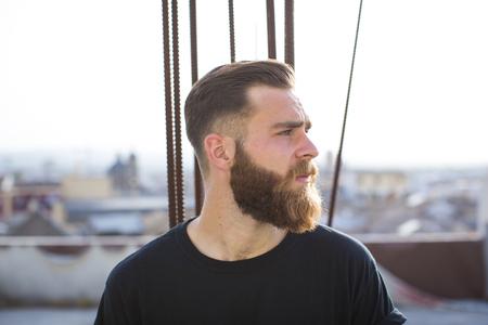 Bearded man posing in the street looking right. Standard-Bild