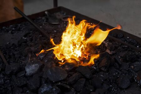 Blacksmith preparing the work piece that is on fire in the blacksmith shop Reklamní fotografie