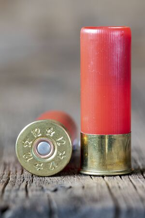 Selective approach of 12-gauge shotgun cartridges used for hunting, on a wooden table