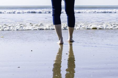 woman in jeans and barefoot walking on the shore of the beach. healthy and relax
