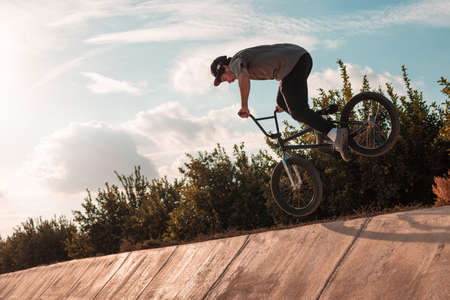 young bmx rider wearing a cap doing a footjam tailwhip on a ramp with the bike Imagens