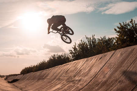young bmx rider wearing a white helmet jumping on a ramp with the bike Banco de Imagens