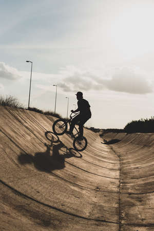 Silhouette of a young male bmx rider steady to jump with the bike on a tube Imagens