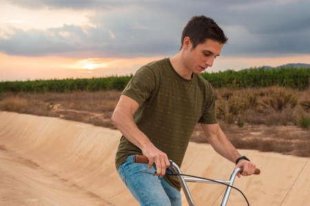 Young dark hair caucassian man riding a bmx bike outdoors