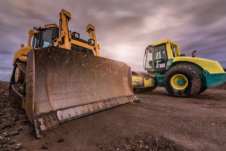 Construction of a dirt road in Spain using an excavator and a steamroller, heavy machinery