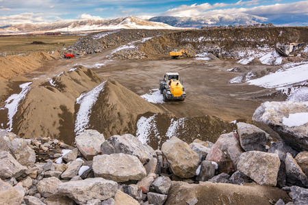 Excavator moving stone in an open pit mine in Spain, mainly granite