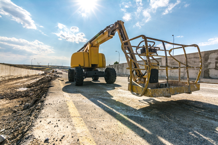 Construction of the pillars of a bridge with a lifting platform. Heavy machinery for construction Stock Photo