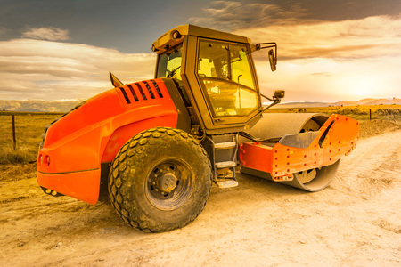 Compactor doing earth compaction work for later asphalting in a road construction Stock Photo