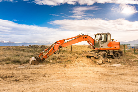 Excavator working on the construction of the expansion works of the Madrid - Segovia - Valladolid highway (Spain). Fundamental work in terrestrial communications Stock Photo