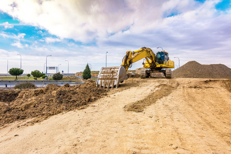 Excavator working on the construction of the expansion works of the Madrid - Segovia - Valladolid highway (Spain). Fundamental work in terrestrial communications 스톡 콘텐츠