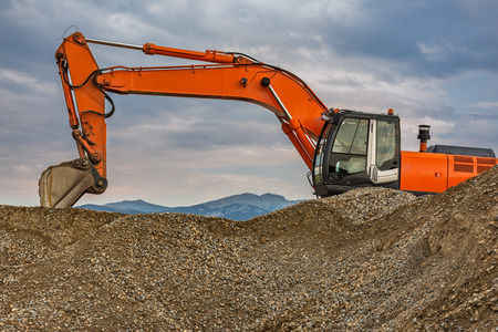 Excavators and heavy machinery in the works of stone movement in a quarry stone extraction for its transformation into gravel Stock Photo