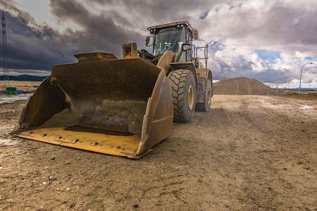 Excavator performing loading and unloading of sand in a construction Stock Photo