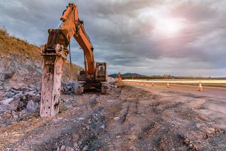 Hydraulic hammer in the works of extension of a highway at the end of the day Stockfoto