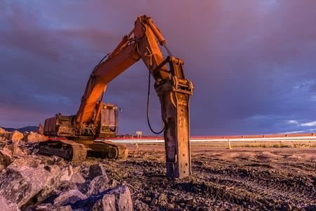 Image de nuit d'un marteau hydraulique dans les travaux d'agrandissement d'une route Banque d'images