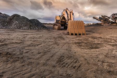 Excavadora y máquina para pulverizar piedra en una cantera Foto de archivo
