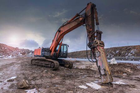 Movimiento de tierra por una excavadora en la construcción de una carretera en España. Martillo hidráulico para retroexcavadora
