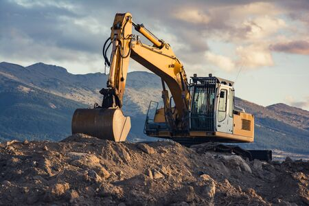 Excavator on top of a dirt mound