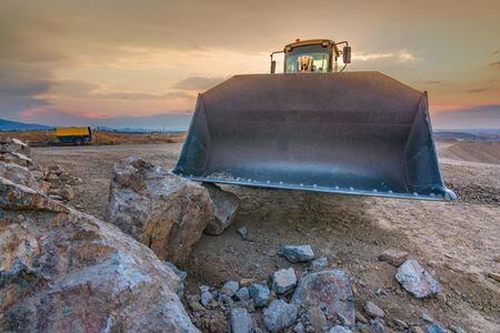 Excavator moving stone and rock in a quarry or at a construction site 写真素材