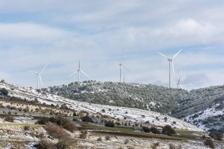Windmills high on a mountain during winter in the interior of Spain