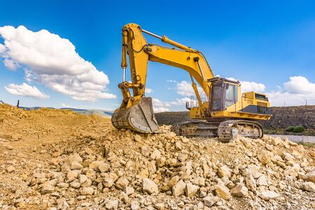 Excavator in a quarry extracting stone and rock