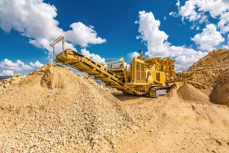 Heavy and mobile machinery in a quarry to transform stone into construction material