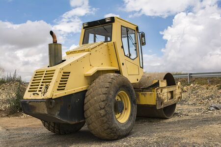 Yellow steamroller doing road construction work