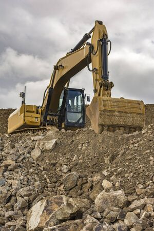 An excavator moves stone and rock in a quarry Standard-Bild