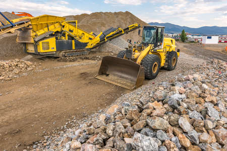 Mechanical conveyor belt and excavator to pulverize rock and stone and generate gravel Standard-Bild