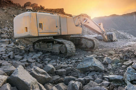 Excavator moving stone and rock at a construction site