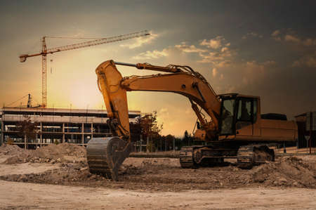 A large excavator at a construction site with cranes and scaffolding in the background Imagens