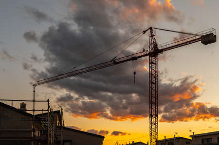 Silhouette of a crane at a construction site at sunset