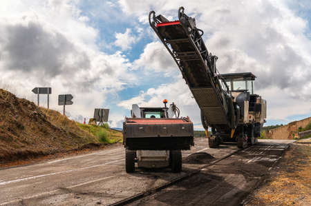 Repair and maintenance work on a road with machinery Imagens