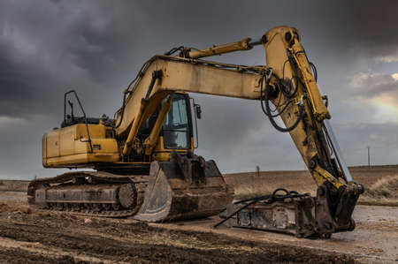 Excavator with hydraulic hammer on road construction works Imagens