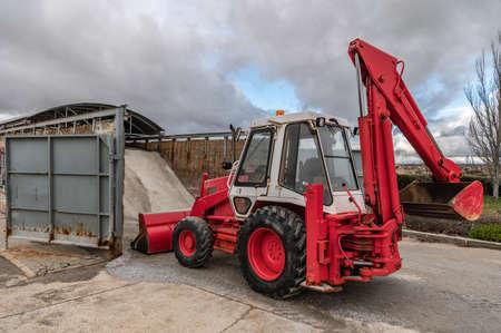 Excavator loading salt for road treatment in winter