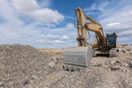 Excavator in a quarry extracting stone