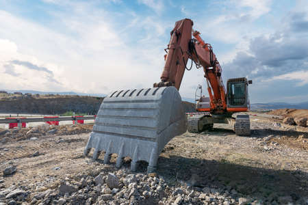 Excavator at the construction site of a road Imagens