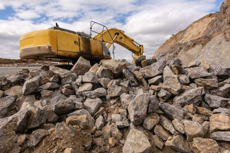 Excavator moving large rocks at a road construction site