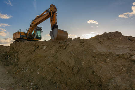Excavator moving dirt and sand at a construction site Stock fotó