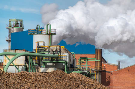 Sugar production factory with chimneys expelling smoke outside