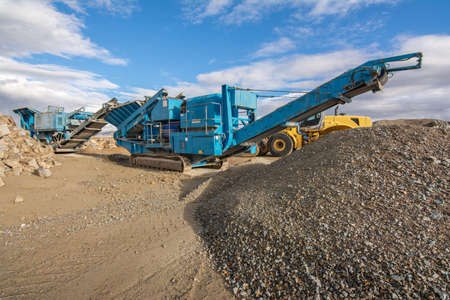 Stone crusher machine in a quarry or open-pit mine, to transform into grave Stock fotó