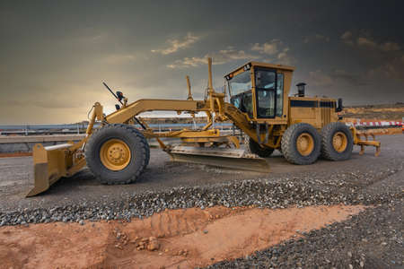 Excavator machine leveling the ground at a road construction site